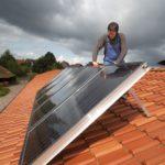 Ein Arbeiter montiert Solarkollektoren auf einem Dach.