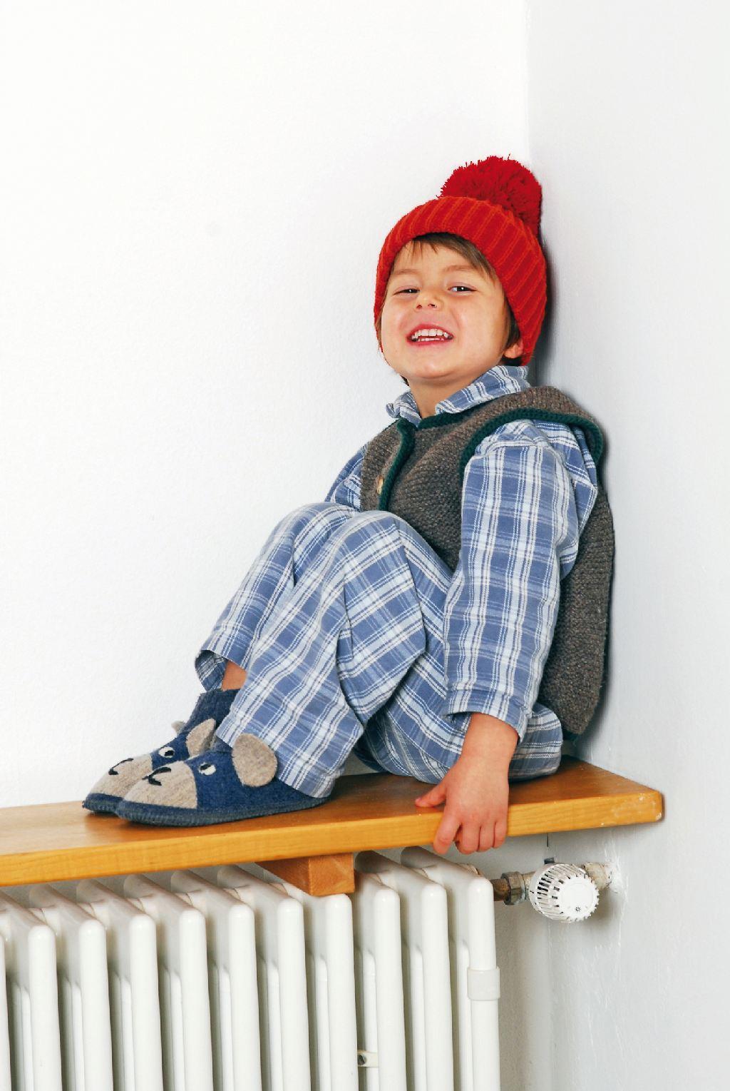 Ein Junge sitzt im Schlafanzug auf einem Heizkörper