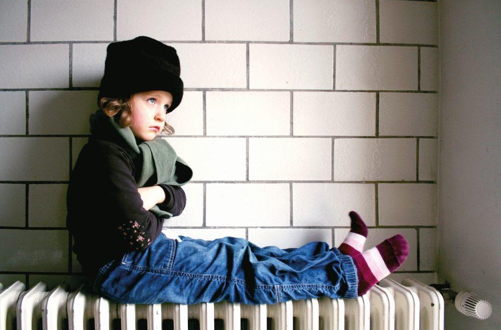Kleines Mädchen sitzt auf einer Heizung. (Heizung defekt)