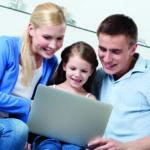 Glückliche Familie sitzt vor dem Laptop. (Heiztechnik)