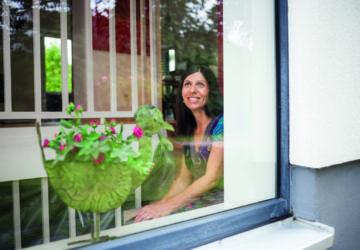 Energetische Modernisierung: glückliche Frau hinter einem Fenster