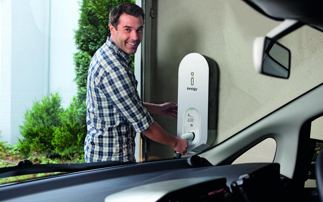 Ein Mann lädt sein Elektroauto auf. Bequem von Zuhause aus in der eigenen Garage.