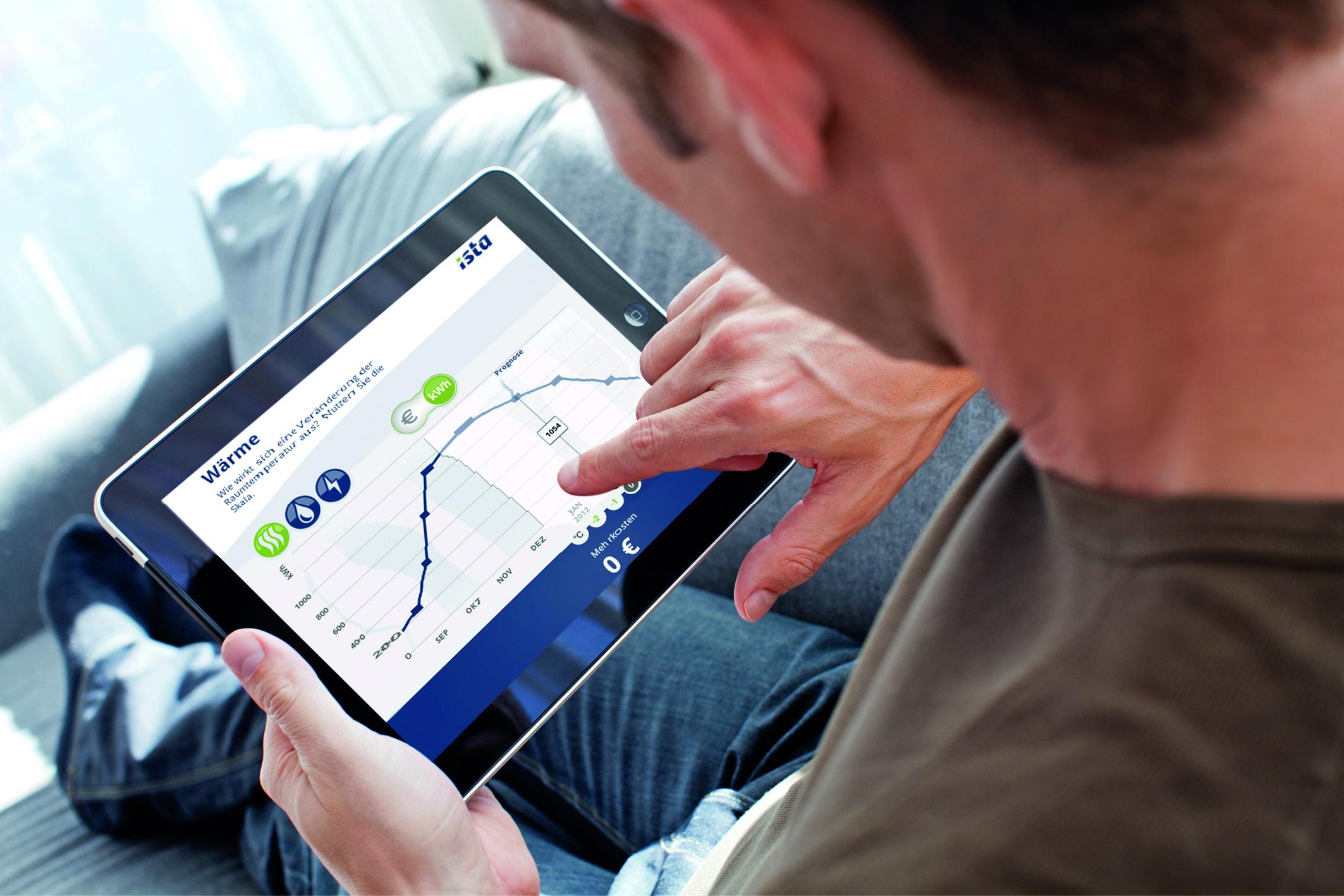 Ein Mann hält ein Tablet in den Händen und kontrolliert auf dem Bildschirm seinen Wärmeverbrauch sowie seine Nebenkosten
