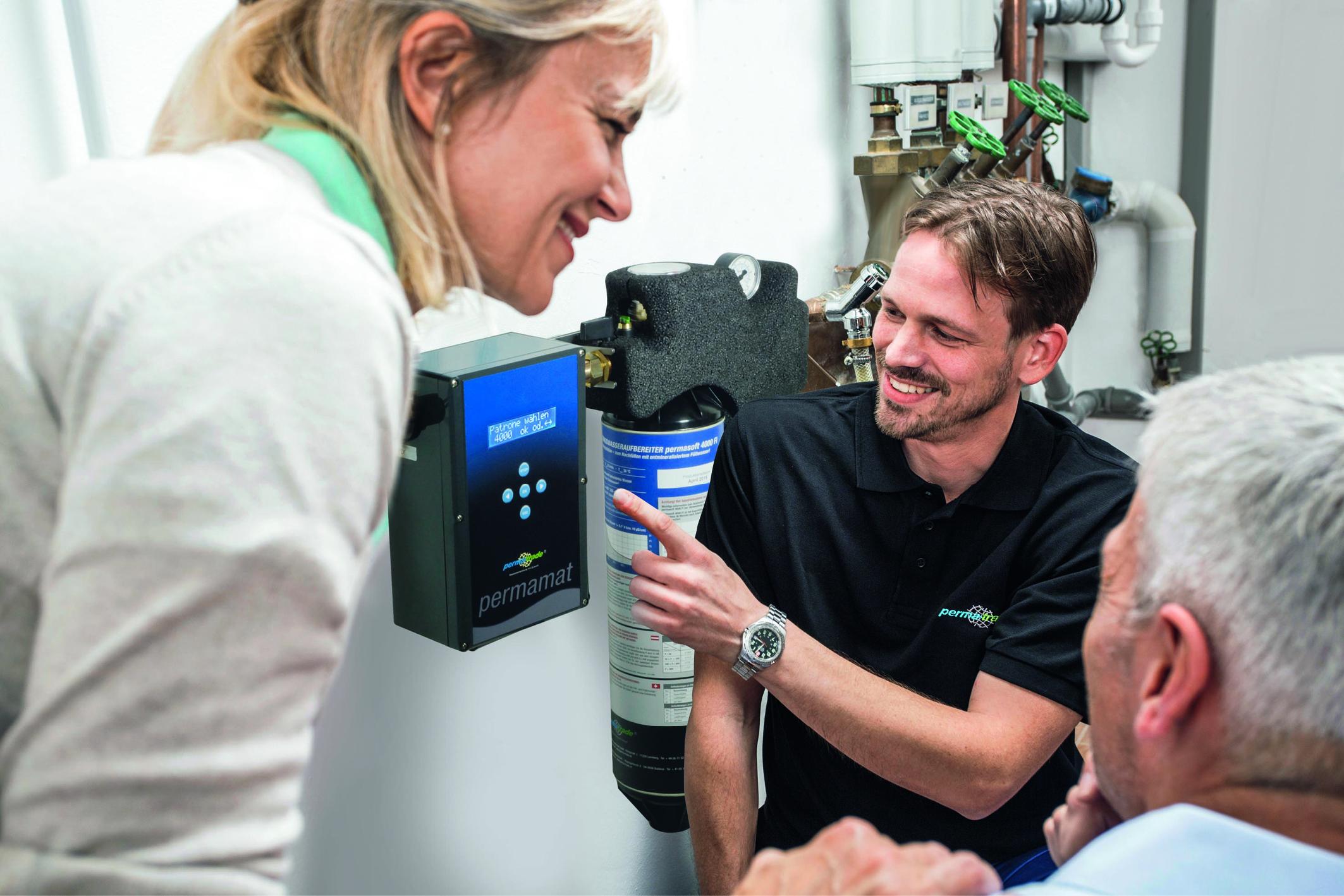 Wechsel des Heizkessels: Ein Fachmann zeigt seinen Kunden ein neues Produkt um Kosten und Nutzen zu optimieren