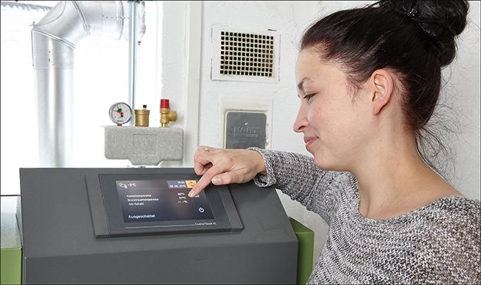 Frau tippt auf das Display einer Pelletheizung
